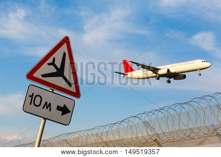 road sign Caution low-flying aircraft on a background of blue sky and aircraft with the gear