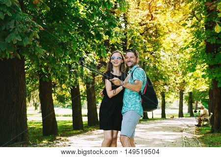 Friends Or Couple Of Lovers Making Selfie Photo On Action Motion Camera In Park Of Europe.