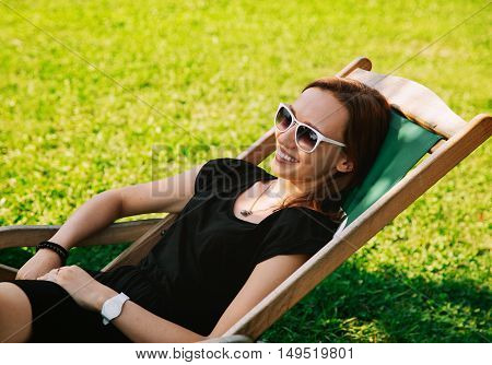 Happy Young Woman Relaxing Outdoor on the Background with Green Grass. Park or Outdoor Cafe. Studing Communicate Holidays Vacation Love and Friendship Concept.