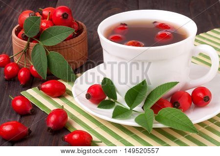 Tea from the hips on the wooden background with green bamboo napkin.