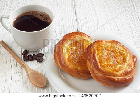 Sweet buns with jam and cup of hot coffee on white wooden table