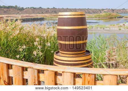 Decorative wooden barrel against beautiful lake and green reed