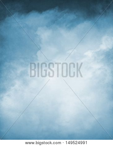An abstraction of clouds and fog on a textured grunge background and toned blue. Image displays a distinct paper grain and texture at 100 percent.