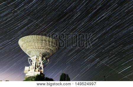 huge white satellite antenna radio telescope on the background of stellar tracks