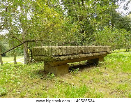 Old stone bench in park with many deciduous trees