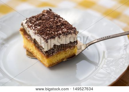 Sponge cake with cream and chocolate on slice on white plate on yellow checkered tablecloth