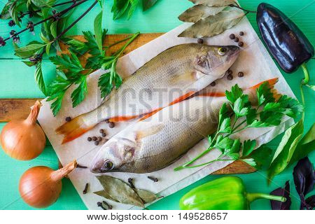 Two raw perch on rustic cutting board with fresh herbs, vegetables and spices on green wooden table. Top view.