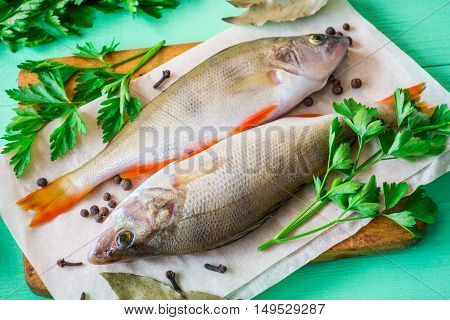 Two raw perch on rustic cutting board with fresh herbs and spices on green wooden table. Top view.