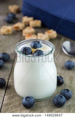 White yogurt in glass jar with honey.
