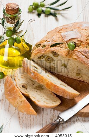 Close-up of bread with olives cut in slices and bottle of olive oil.