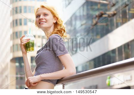 Portrait of smiling caucasian young woman with fresh drink mojito resting on city street