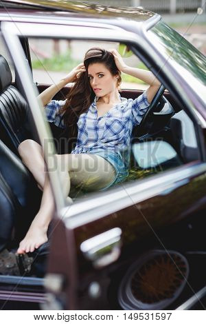 Brunette in short shorts sitting in open car in summer, tinted photo