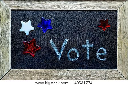 Vote written on blackboard surrounded by red, white and blue stars.  Election symbol for local and national campaigns.