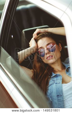 young girl in sunglasses sitting in burgundy car, tinted photo