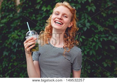 Cheerful ginger girl with cocktail in hand next to hedges, toned photo