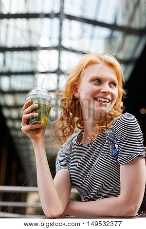 Laughing young redhead woman holding fresh mojito in hand and looking to the side