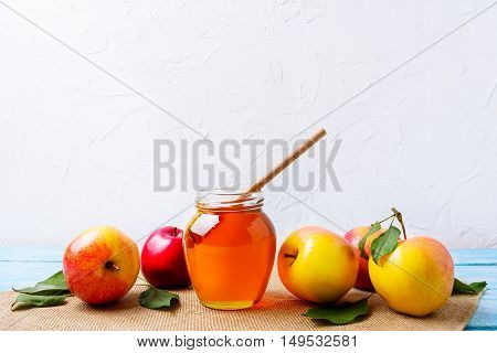 Honey jar with dipper and apples on white background. Rosh hashanah concept. Jewesh new year symbols. Copy space.