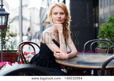 young woman in black dress sitting at table in cafes
