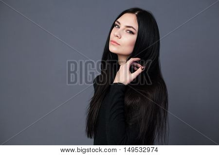 Brunette woman with beautiful long hair gray background