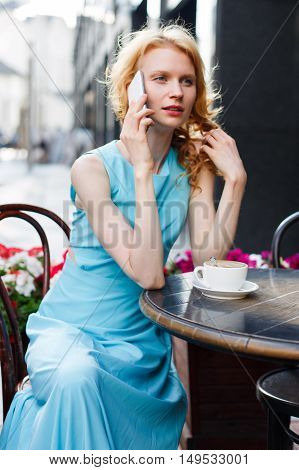young red-haired girl talking on phone at cafe summer