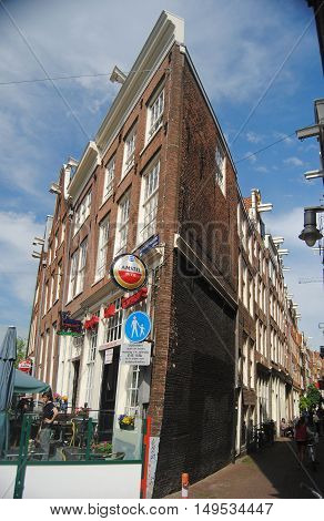 Amsterdam, The Netherlands - May 22, 2014. Street view in Amsterdam. Leaning historic building along Nieuwezijds Voorburgwal street in Amsterdam, with outdoor cafe and people.