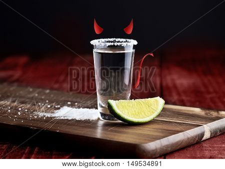 Tequila silver shot with lime slice devil colors on grunge wooden board