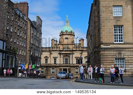 Edinburgh, United Kingdom - June 14, 2014. Street view on intersection of the Royal Mile and Lawnmarket, toward the Museum on the Mound, with historical buildings, people and cars.