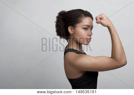 Studio shot of a young woman flexing her muscles