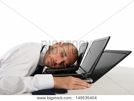 Businessman sleeping over computers on the desk