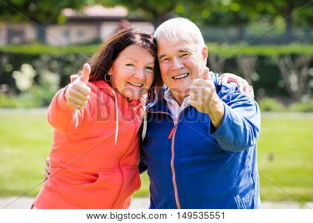 Portrait Of Smiling Senior Couple Showing Thumbs Up
