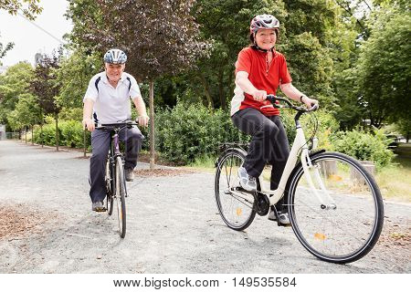 Smiling Elderly Senior Couple Cycling In Park At Morning