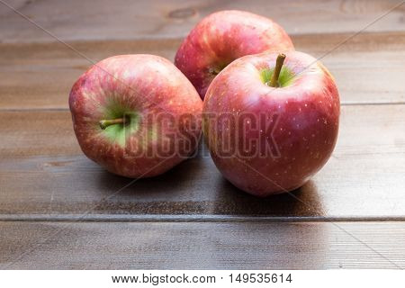 Three Apples On The Wooden Table