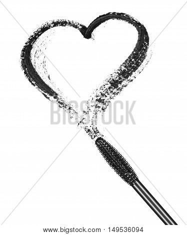 Stroke of black mascara in the form of heart with applicator brush close-up isolated on white background