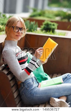 Girl spectacled with notebooks sitting on bench on street
