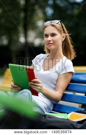 Young girl with tablet in their hands sitting on park bench amid nature