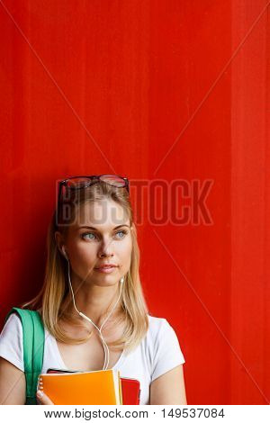 Student with sunglasses and headphones on background blank red Wall