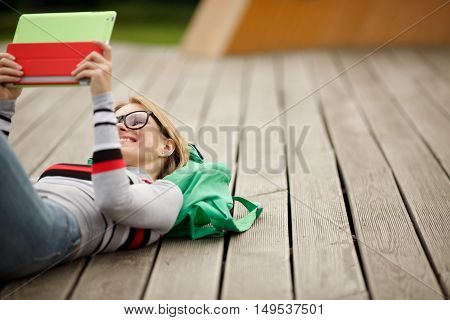 girl in black glasses looks into tablet on wooden stage