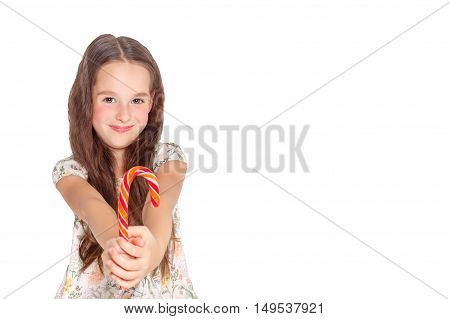 Happy, smiling cute little girl eating cristmas candy cane, Isolated on white.