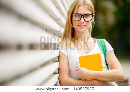 Student girl in glasses with notebooks near wooden walls in summer
