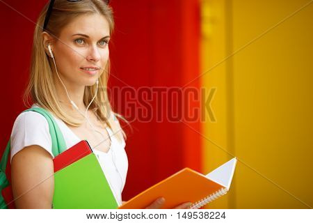 Smiling girl with open notebook and Tablet near Wall
