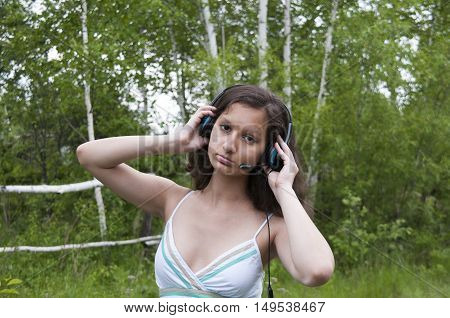Girl with headphones listening to music in the woods
