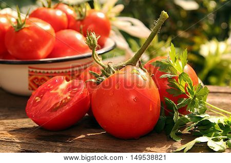 Bunch of fresh ripe tomatoes and half of cutted tomato against background tomatoes in bowl and white flowers