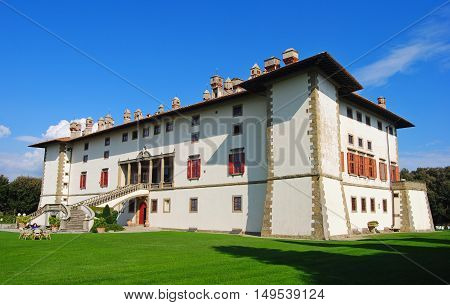Artimino, Italy - October 6, 2014. Villa Medicea in Artimino, Tuscany, with grass lawn and people. Also known as the villa of the 100 chimneys for the numerous chimneys still visible on its roof, it was built at the end of the 16th century and is listed a