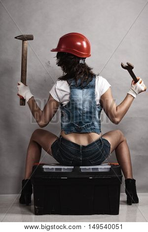 Sex equality and feminism. Back of sexy girl sitting on toolbox holding wrench spanner and hammer. Woman working as mechanic.