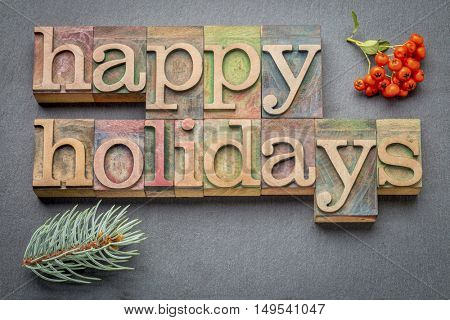 Happy Holidays banner or greeting card in letterpress wood type blocks against slate stone