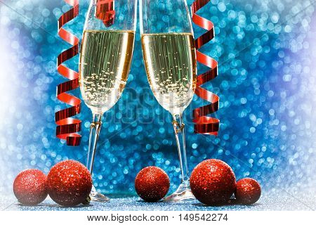 Two champagne glasses, decoration on glitter background