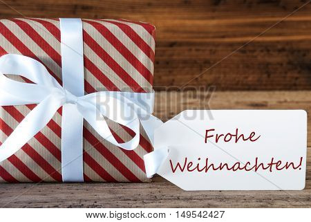 Macro Of Christmas Gift Or Present On Wooden Background. Card For Seasons Greetings, Best Wishes Or Congratulations. White Ribbon With Bow. German Text Frohe Weihnachten Means Merry Christmas