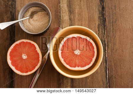 Fresh halved pink grapefruit served in a bowl for breakfast with caramelized sugar and spoons on a wooden table with copy space overhead view