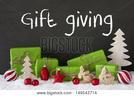 English Text Gift Giving. Green Gifts Or Presents With Christmas Decoration Like Tree, Moose Or Red Christmas Tree Ball. Black Cement Wall As Background With Snow.