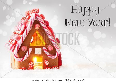 Gingerbread House In Snowy Scenery As Christmas Decoration. Candlelight For Romantic Atmosphere. Silver Background With Bokeh Effect. English Text Happy New Year